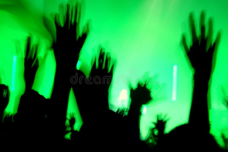 Raving people. People lifting their hands while dancing in the discotheque stock photo