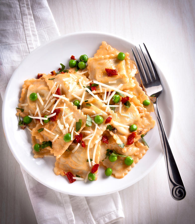 Ravioli. A plate with ravioli in pea prosciutto sauce royalty free stock images