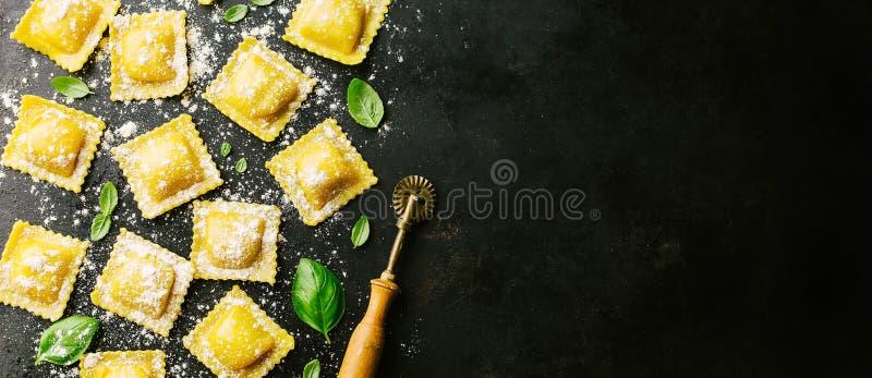 Ravioli crudi con basilico e farina su buio fotografie stock