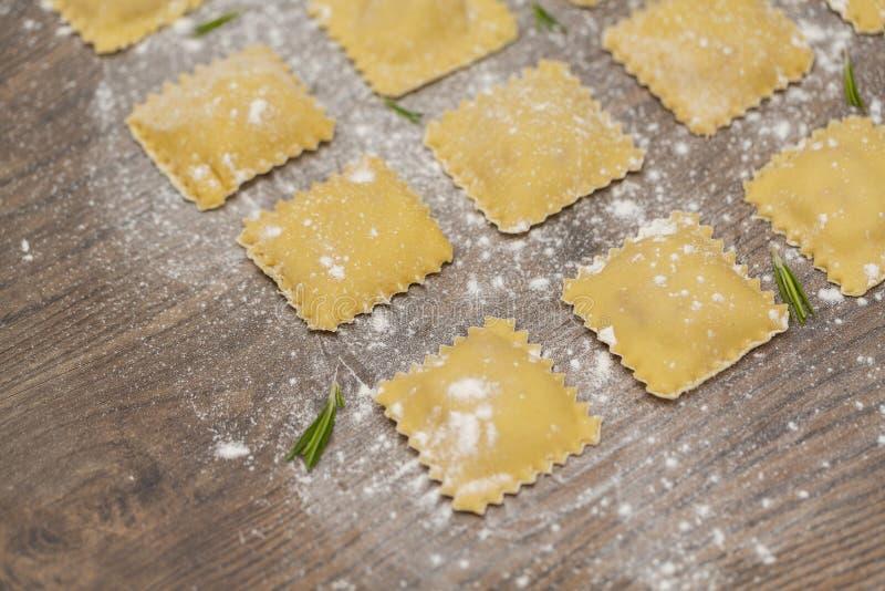 Ravioli crudi saporiti con farina su fondo di legno Processo di produrre ravioli italiani immagini stock