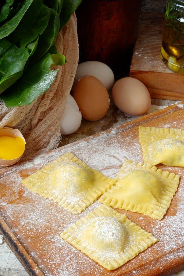 Ravioli crudi saporiti con la ricotta e gli spinaci, con farina e le uova su fondo di legno Processo di produrre ravioli italiani fotografie stock libere da diritti