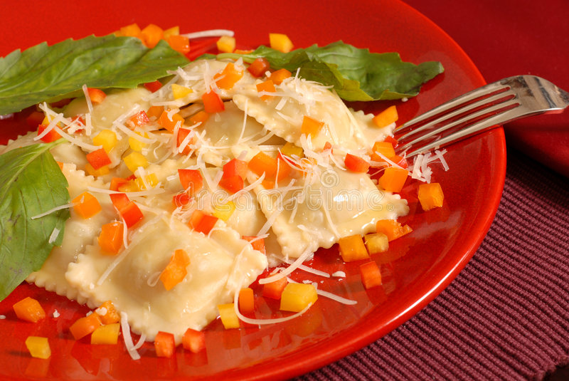 Ravioli die met gedobbelde rode, gele en oranje peper met ba wordt bedekt stock foto's