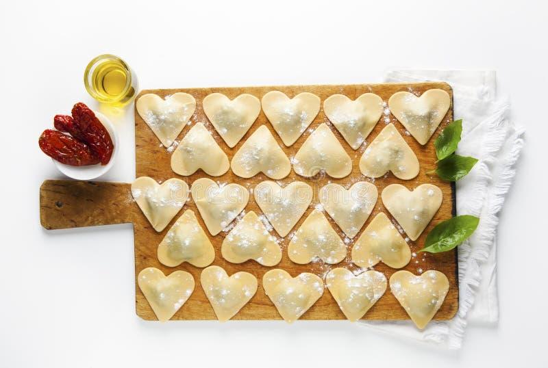 Ravioli i en hjärtaform skärbräda med en grupp av rå fres arkivfoton