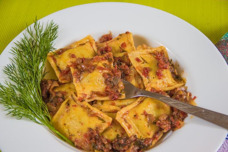 Ravioli italiens de pâtes avec la sauce tomate et le vert photo stock