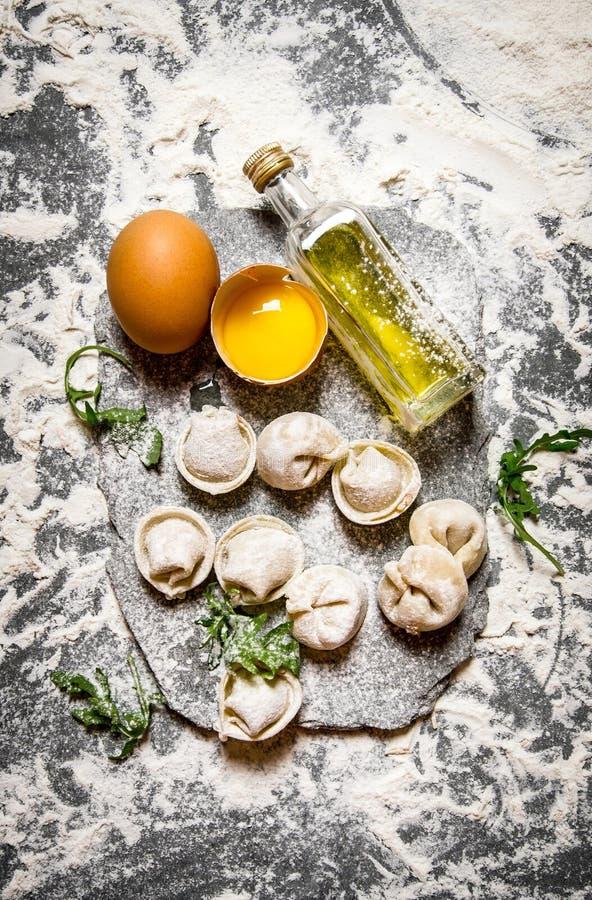 Ravioli med ägg, olivolja och örter På stentabellen med mjöl royaltyfri foto
