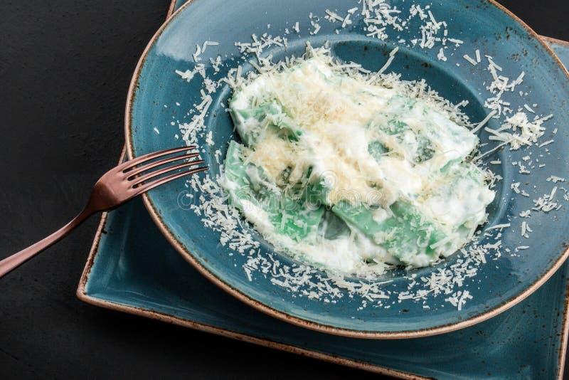 Ravioli met spinazie en basilicum, parmezaanse kaaskaas op plaat over zwarte steenachtergrond Het schone eten, vegetarisch voedse royalty-vrije stock foto