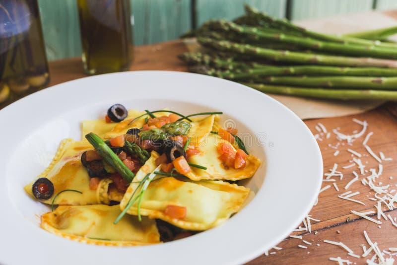 Ravioli mit Oliven, Spargel und Tomate lizenzfreie stockfotos