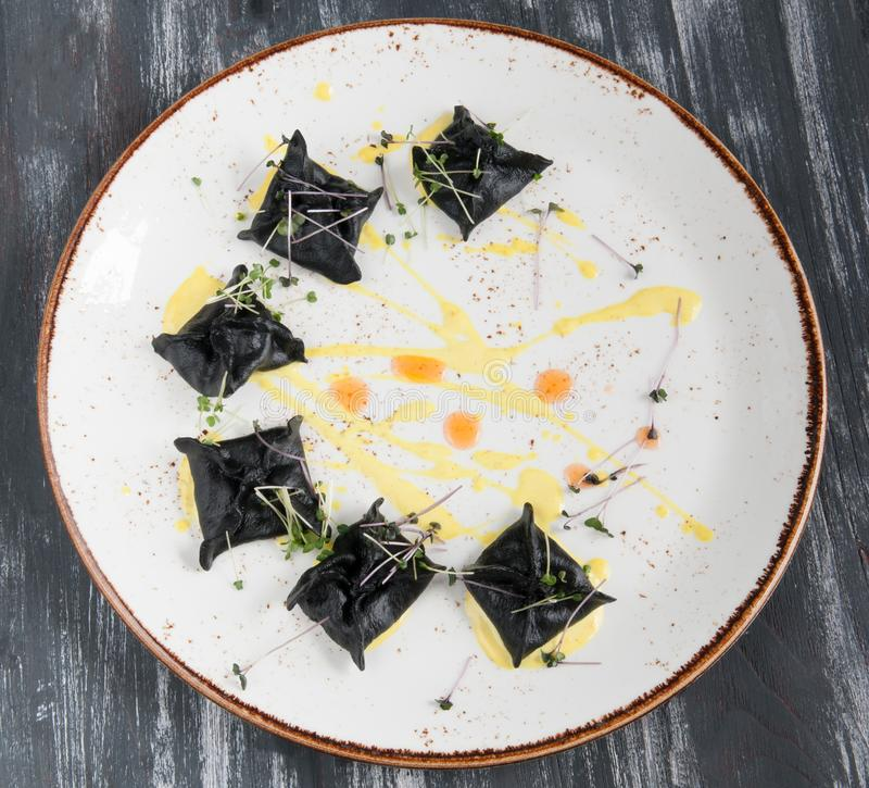 Ravioli neri con frutti di mare Su una vista superiore del piatto Su fondo nero di legno fotografia stock libera da diritti