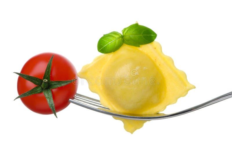 Ravioli pasta tomato and basil on fork royalty free stock photography