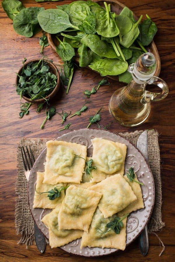 Ravioli prêts dans un plat, épinards, huile d'olive dans un pot image stock