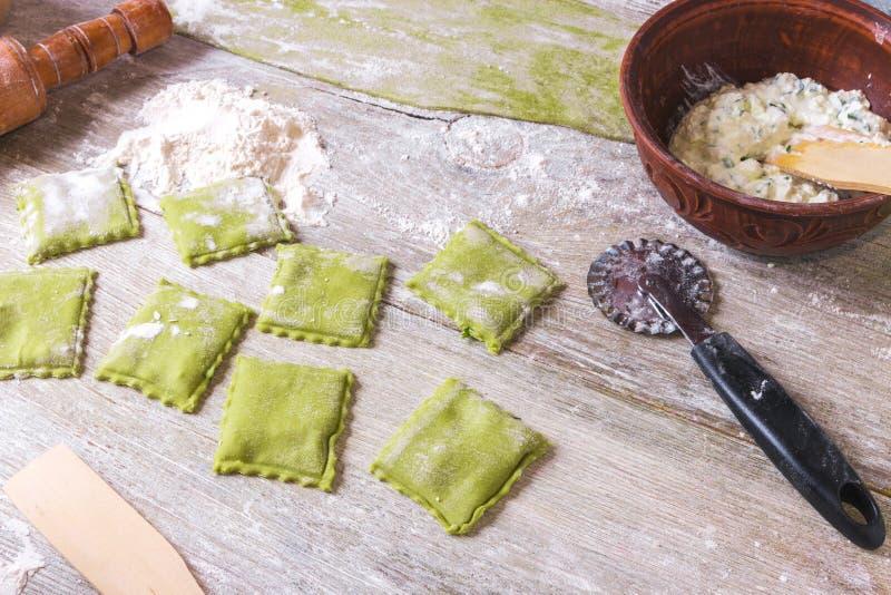 Ravioli verts crus faits maison d'épinards avec du fromage et le persil de ricotta sur un fond rustique en bois photographie stock libre de droits