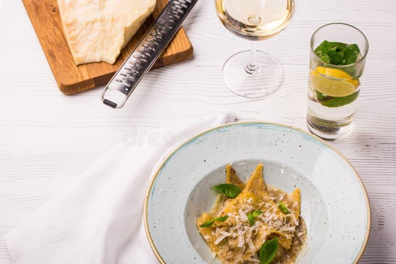 Raviolideegwaren met basilicum en parmezaanse kaaskaas op plaat Parmezaanse kaas met een rasp op een scherpe raad stock foto