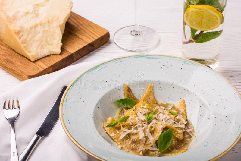 Raviolipasta med basilika- och parmesanost på plattan Parmesan med ett rivjärn på en skärbräda arkivbild