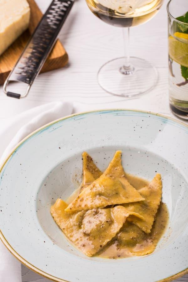 Raviolipasta med basilika- och parmesanost på plattan Parmesan med ett rivjärn på en skärbräda Vertikalt foto royaltyfri bild