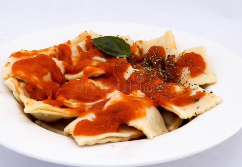 Raviolis con una salsa boloñesa deliciosa, rematada con albahaca fresca imágenes de archivo libres de regalías