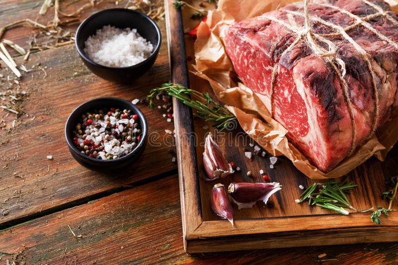Raw aged prime black angus beef in craft papper on rustic wood. Raw black angus beef bound with rope in craft paper on cutting board. Aged prime marble meat stock image