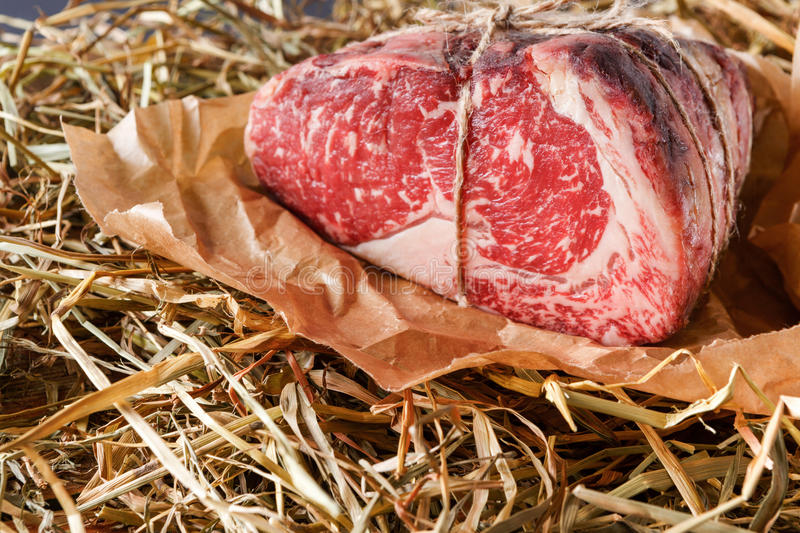 Raw aged prime black angus beef in craft papper on straw royalty free stock images