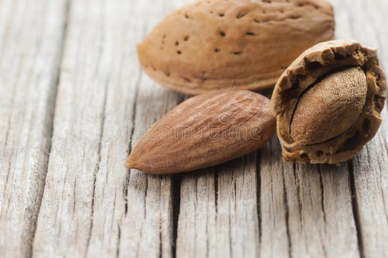Raw almond nut in shell on wooden table. Almonds background concept. royalty free stock photography