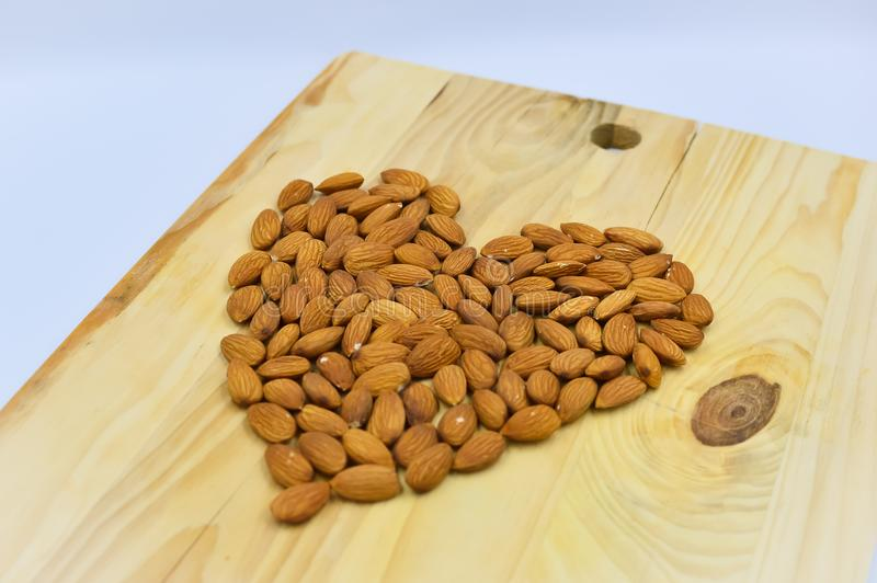 Almond heart on the wood. Raw almonds in shape of hart on the wooden background royalty free stock image
