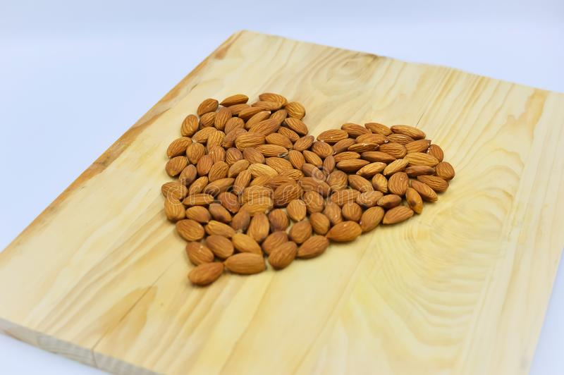 Almond heart on the wood. Raw almonds in shape of hart on the wooden background stock images