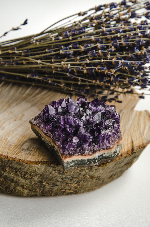 Raw amethyst rock with bunch of aromatic lavender flowers on natural wood rustic esoteric stock photo