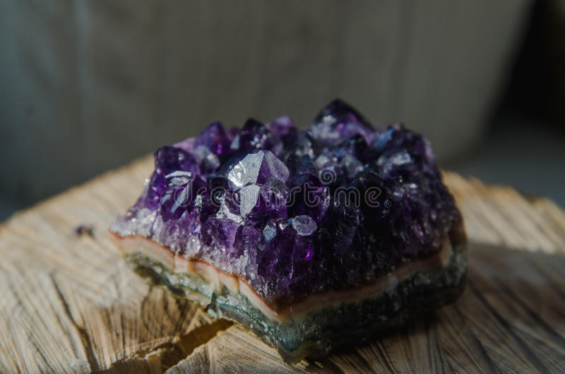 Raw amethyst rock with reflection on natural wood crystal ametist. Raw violet amethyst rock with reflection on natural wood macro crystal ametist esoteric royalty free stock images