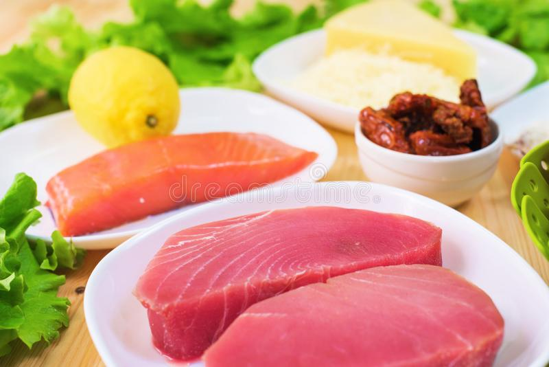 Raw appetizing fillet of tuna on a table with a yard of Greek salad with salmon and lemon cucumbers and tomatoes as well. As cheese. The concept of a delicious stock photography