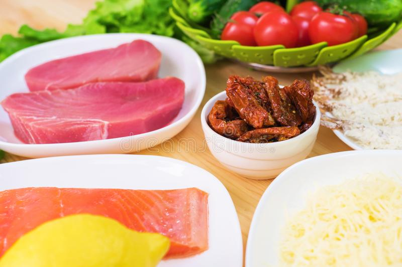 Raw appetizing fillet of tuna on a table with a yard of Greek salad with salmon and lemon cucumbers and tomatoes as well. As cheese. The concept of a delicious royalty free stock photos