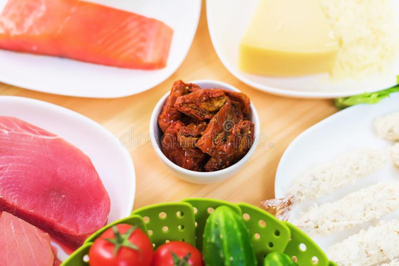 Raw appetizing fillet of tuna on a table with a yard of Greek salad with salmon and lemon cucumbers and tomatoes as well. As cheese. The concept of a delicious stock images