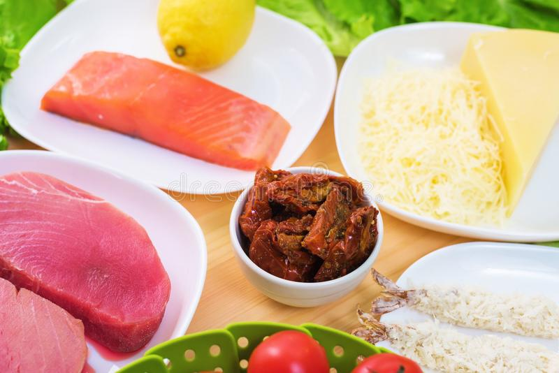 Raw appetizing fillet of tuna on a table with a yard of Greek salad with salmon and lemon cucumbers and tomatoes as well. As cheese. The concept of a delicious stock photo