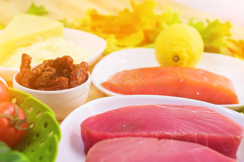 Raw appetizing fillet of tuna on a table with a yard of Greek salad with salmon and lemon cucumbers and tomatoes as well. As cheese. The concept of a delicious stock photos
