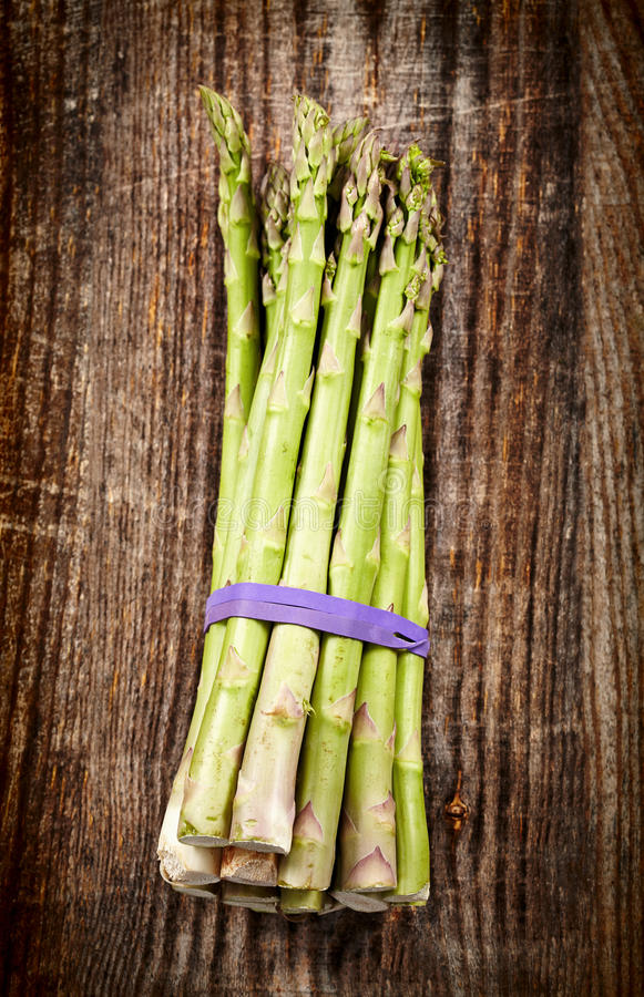 Raw asparagus on wooden board royalty free stock photo