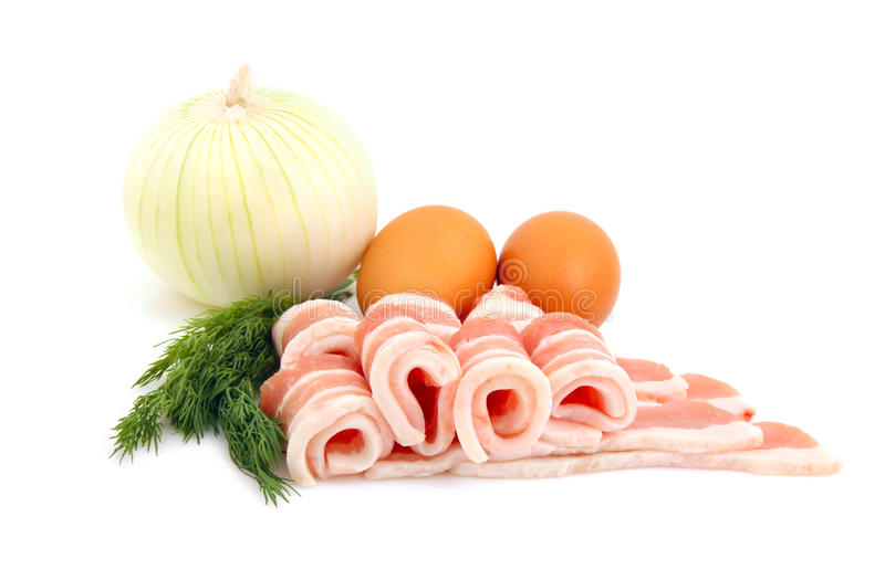 Raw bacon, eggs and onion. Food ingredient for the breakfast - raw bacon rashers, eggs, onion and fennel. Isolated on white background royalty free stock photography