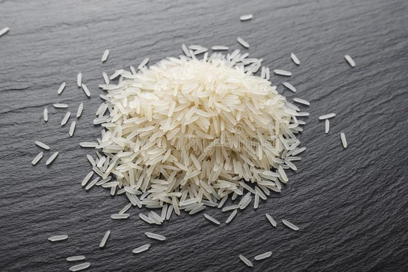 Raw basmati rice. The raw basmati rice is scattered on a black slate. place for text royalty free stock image