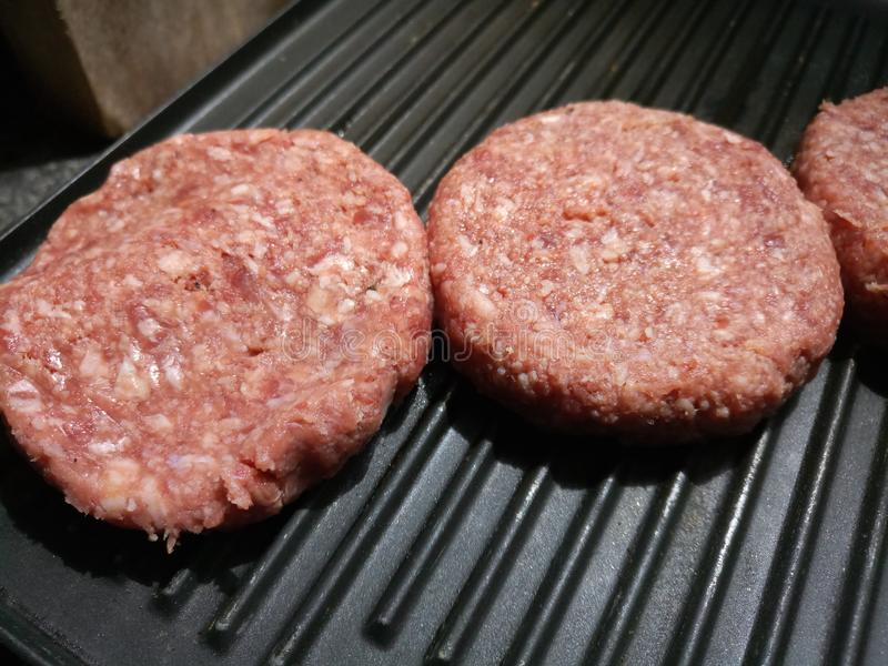 Raw beef burgers on a hot grill stock image