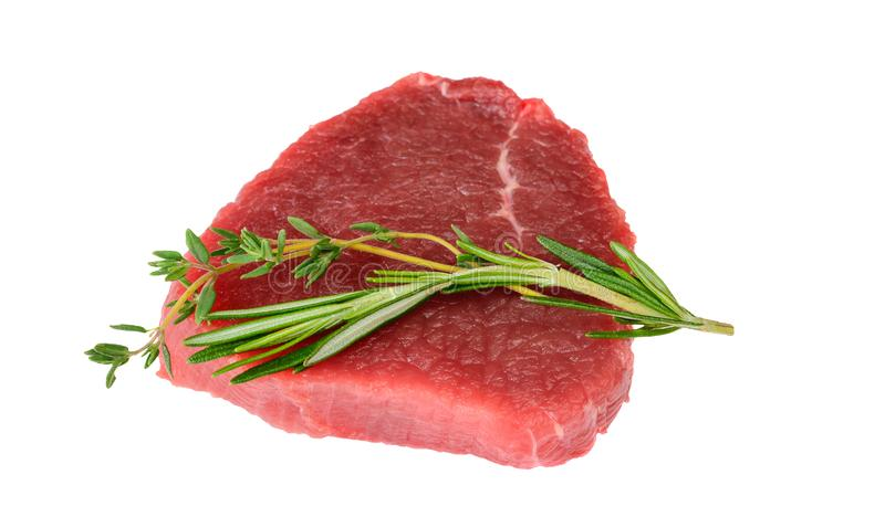Raw beef filet mignon steak with rosemary and thyme herbs on white. Background royalty free stock photo