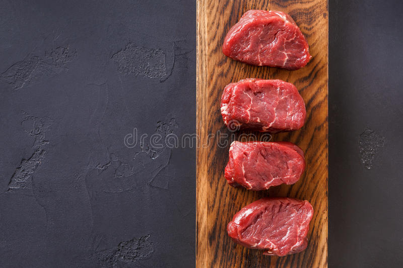 Raw beef filet mignon steaks on wooden board at gray background royalty free stock image