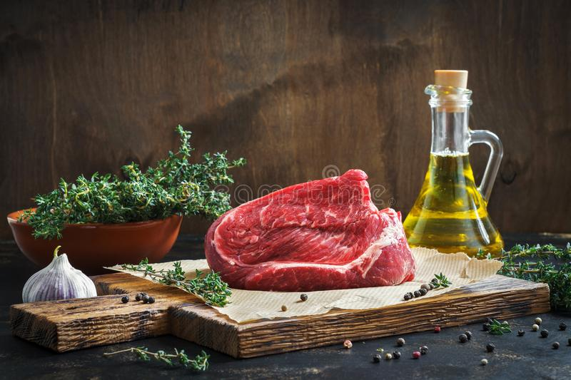 Raw beef fillet on a cutting board, thyme, olive oil. Ingredients for the preparation of stacks. royalty free stock photography