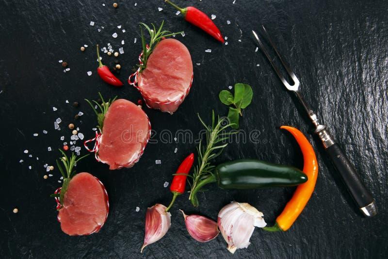 Raw beef fillet steaks mignon on dark background stock image
