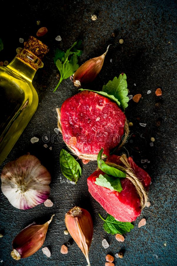 Raw beef fillet steaks mignon. With spices and herbs on dark concrete table background royalty free stock photos