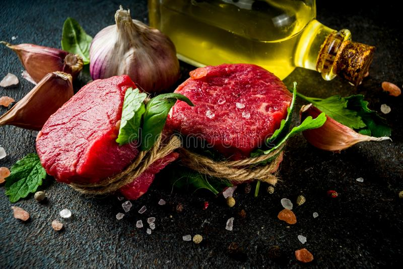 Raw beef fillet steaks mignon. With spices and herbs on dark concrete table background royalty free stock photography