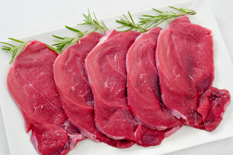 Raw beef fillets. Closeup of some raw beef fillets on a plate on a white background stock images
