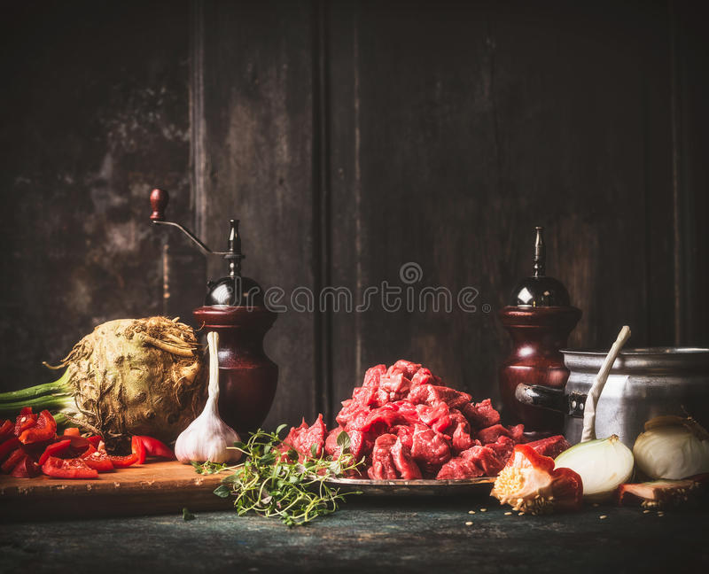 Raw Beef goulash with vegetables and cooking ingredients on dark rustic kitchen table stock image