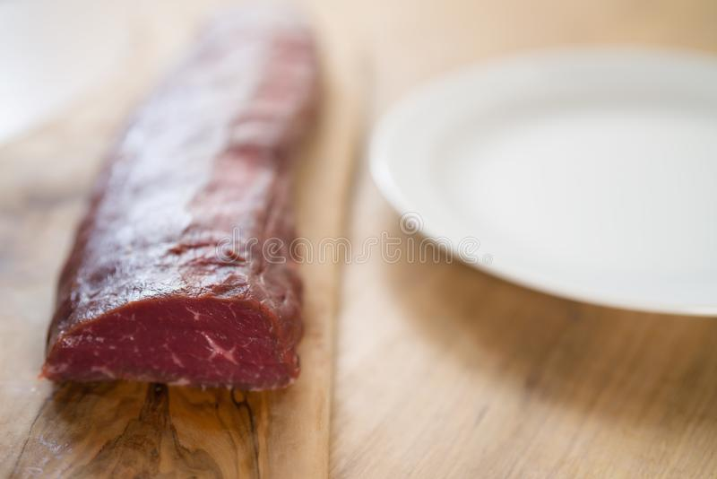 Raw beef for making filet mignon steaks on wood board. Shallow focus royalty free stock photography