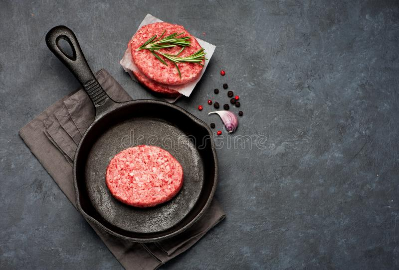 Raw Beef Meat Burger cutlets and spices in a cast-iron frying pan. royalty free stock image