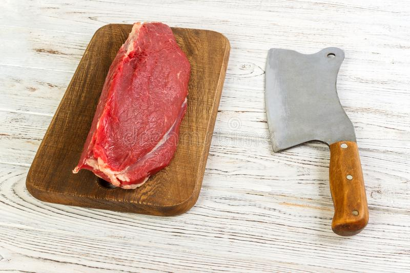 Raw beef meat on cutting board with old vintage cleaver.  royalty free stock photos