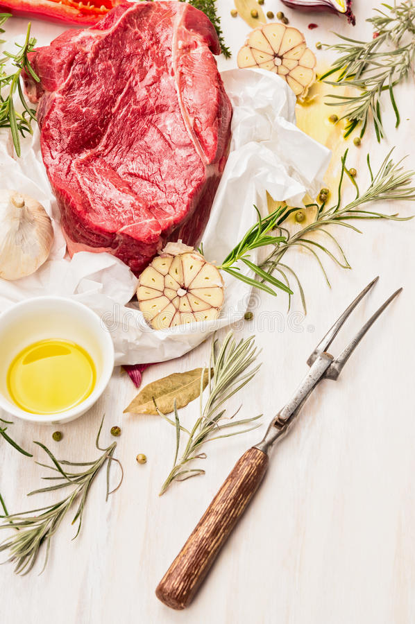 Raw beef meat with oil, spices, meat fork and fresh flavoring on white paper, preparation for cooking. Or grill royalty free stock images