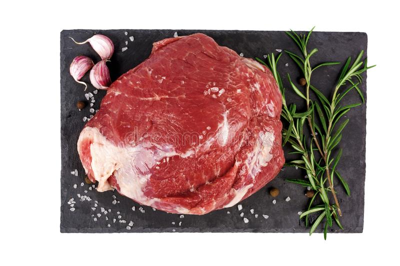 Raw beef meat with rosemary and garlic on a black slate isolated on white background royalty free stock photos