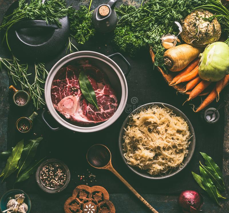 Raw beef meat shin with bone in cooking pot with spices and bowl with pickled cabbage on dark kitchen tables background royalty free stock image
