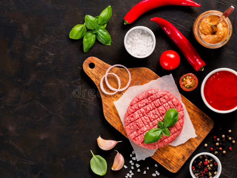 Raw beef meat steak cutlet for burger with spices and vegetables stock image
